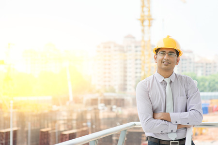 Portret van Aziatische Indiase man website aannemer ingenieur met harde hoed bedrijf blauwdruk papier lachend op bouwplaats, kraan met gouden zonlicht op de achtergrond. Stockfoto
