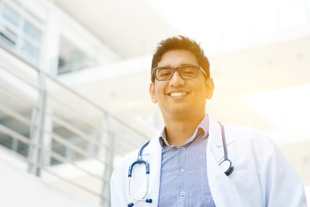 asian american: Portrait of Asian Indian medical doctor smiling and looking at camera, standing outside hospital building, beautiful golden sunlight at background.