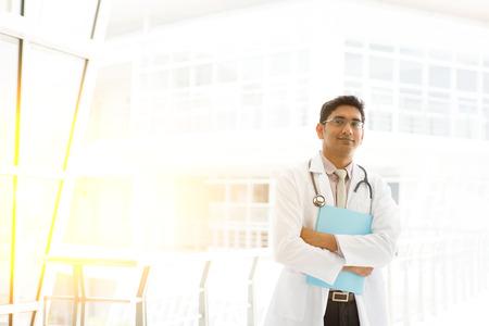pakistani ethnicity: Portrait of Asian Indian medical doctor holding file folder, standing outside hospital building block, beautiful golden sunlight at background.