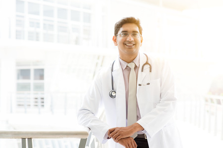 pakistani ethnicity: Portrait of successful Asian Indian medical doctor smiling and standing outside hospital building, beautiful golden sunlight at background.