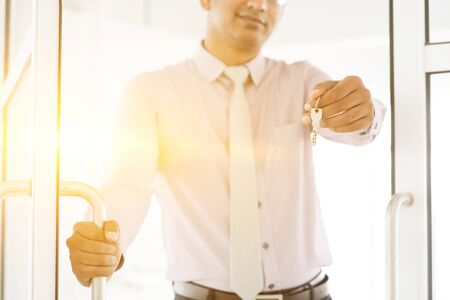 key handover: Asian Indian man holding office key, focus on the key, golden sunlight at background.