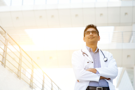 Portrait of confident Asian Indian medical doctor standing outside hospital building, beautiful golden sunlight at background.