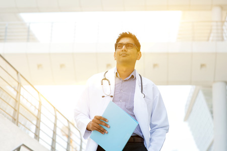 medical people: Portrait of Asian Indian medical doctor standing outside hospital building, beautiful golden sunlight at background. Stock Photo