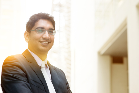 thirties portrait: Portrait of Asian Indian business man smiling, outside modern office building block, beautiful golden sunlight at background. Stock Photo