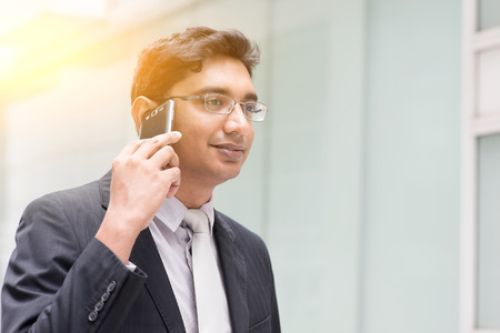 happy worker: Portrait of Asian Indian business man using smartphone, outside modern office building block, beautiful golden sunlight at background.