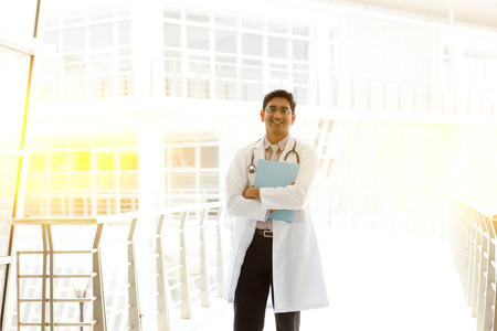 pakistani ethnicity: Portrait of Asian Indian medical doctor holding medical report, standing outside hospital building block, beautiful golden sunlight at background.