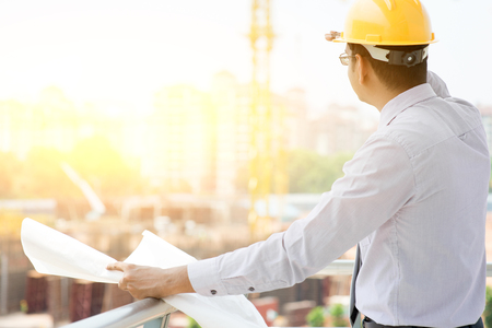 Asian Indian male site contractor engineer with hard hat holding blue print paper looking away inspecting progress at construction site, crane with golden sunlight at the background. Banque d'images