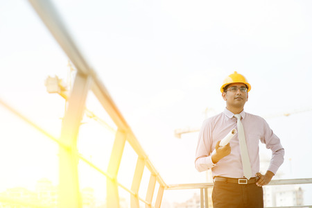 Portrait of Asian Indian male site contractor engineer with hard hat holding blue print paper at construction site, crane with golden sunlight at the background.