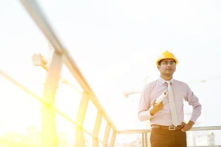 ingeniero civil: Retrato del ingeniero contratista sitio masculina india asiática con el sombrero duro que sostiene el papel de impresión azul en lugar de construcción, grúa con la luz del sol de oro en el fondo.