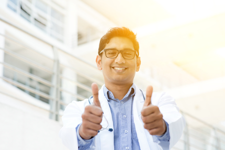 pakistani ethnicity: Portrait of Asian Indian medical doctor smiling and thumbs up, standing outside hospital building, beautiful golden sunlight at background. Stock Photo