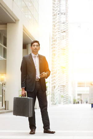 native american man: Portrait of fullbody Asian Indian business man standing outside modern office building block, beautiful golden sunlight at background. Stock Photo