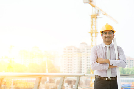 Portrait of Asian Indian male site contractor engineer with hard hat holding blue print paper looking at camera and smiling at construction site, crane with golden sunlight at the background.