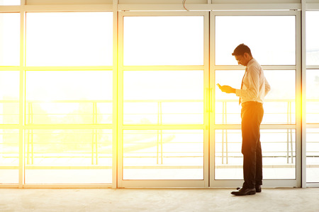 businessman waiting call: Asian Indian businessman using mobile phone in modern office building, golden sunset background.