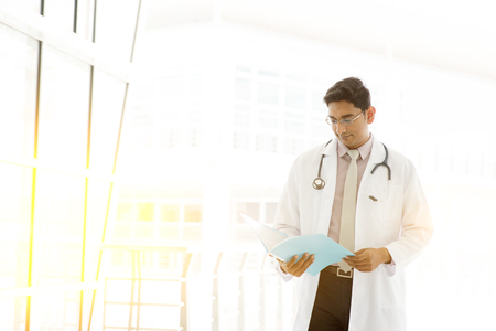 pakistani ethnicity: Portrait of handsome Asian Indian medical doctor walking and reading on medical report, outside hospital building block, beautiful golden sunlight at background. Stock Photo