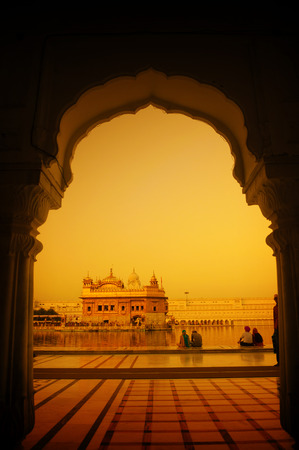 temple tank: Amritsar Golden Temple, India. Framed with windows from west side in sunset. Focus on temple. Stock Photo