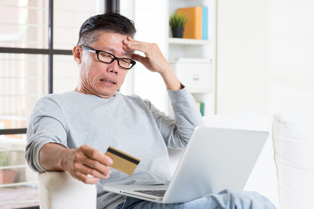 bill payment: Portrait of 50s mature Asian man having problems while using computer internet doing online payment with credit card, sitting on sofa at home. Stock Photo