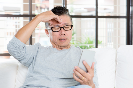 Portrait of 50s mature Asian man headache while using smart phone, sitting on sofa at home.