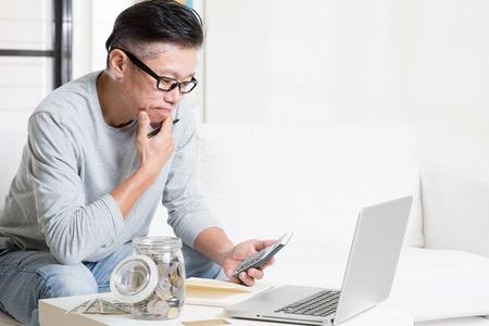 Aziatische volwassen man rekenen op geld met behulp van een rekenmachine en laptop computer. Saving, pensioen, gepensioneerden financiële planning concept. Familie wonen levensstijl thuis. Stockfoto - 49463075