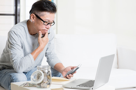 Asian mature man counting on money using calculator and laptop computer. Saving, retirement, retirees financial planning concept. Family living lifestyle at home.