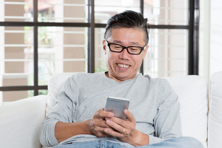 Portrait of 50s mature Asian man texting using smart phone, sitting on sofa at home.