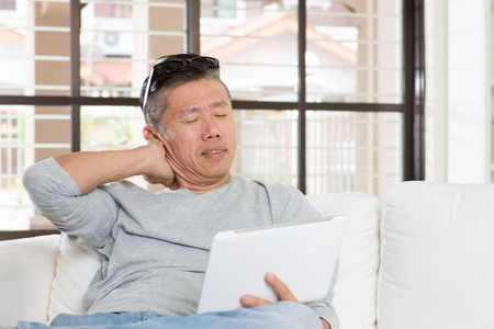 Portrait of 50s mature Asian man shoulder pain, pressing on neck with tired expression after long period using tablet computer, sitting on sofa at home.