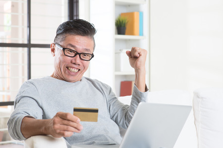 one person: Portrait of 50s mature Asian man winning prizes while using computer internet doing online payment with credit card, sitting on sofa at home.