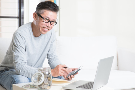 cashflow: Mature 50s Asian man counting on money using calculator and laptop computer. Saving, retirement, retirees financial planning concept.