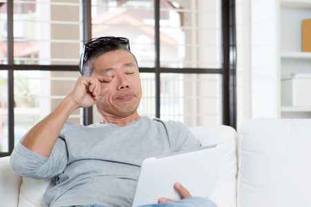 Portrait of 50s mature Asian man eyes pain, rubbing eye with tired expression after long period using tablet computer, sitting on sofa at home.