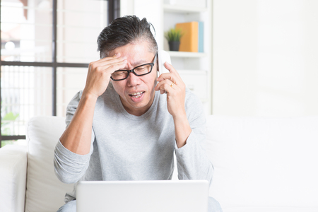 50s: Portrait of 50s mature Asian man having problems and calling on phone, using computer internet working from home, sitting on sofa indoors. Stock Photo