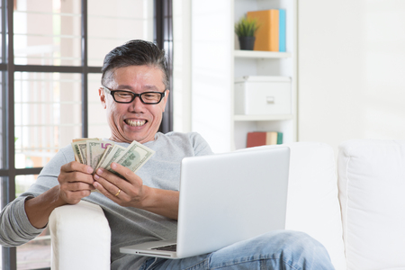 money online: Portrait of happy 50s mature Asian man using internet computer and counting cash at home, earning money from his successful online business. Working from home concept.