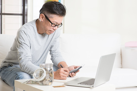 retirees: Asian mature man counting on money using calculator and laptop computer. Saving, retirement, retirees financial planning concept. Stock Photo