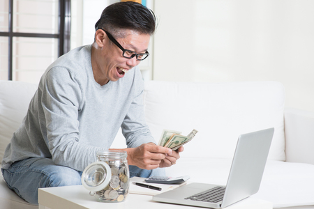invest: Mature 50s Asian man counting on money with excited face expression. Saving, retirement, retirees financial planning concept.