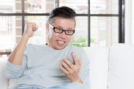 Portrait of excited 50s mature Asian man celebrating success while using smart phone, sitting on sofa at home. Stock Photo