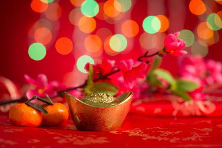 flores chinas: Chino nuevo año decoraciones del festival, lingotes de oro, flor de ciruela y mandarina en el fondo rojo del brillo. Foto de archivo