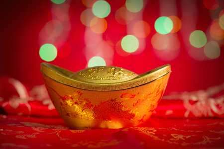 gold ingot: Chinese new year decorations, gold ingot on red glitter background.