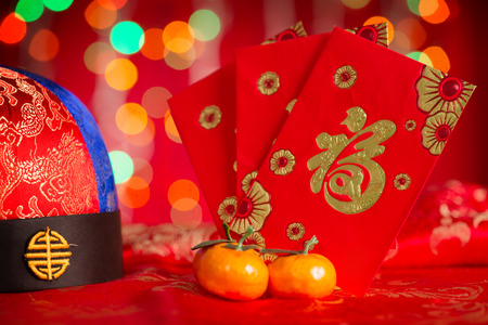 packet: Chinese new year festival decorations, red packet and mandarin orange on red glitter background. Chinese character means good fortune, not logo and copyright. Stock Photo