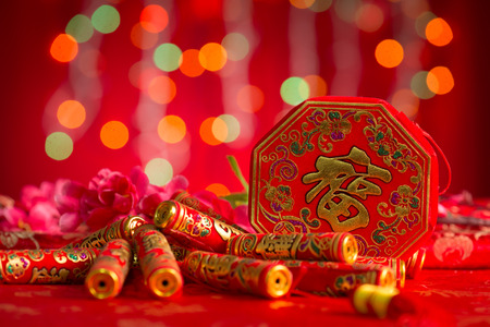 Chinese new year festival decorations, plum flower and firecrackers on red glitter background.