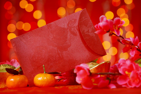 ang: Chinese new year festival decorations, ang pow or red packet with copy space ready for text, on glitter red background.