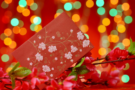 red packet: Chinese new year festival decorations, ang pow or red packet and plum flower. Stock Photo