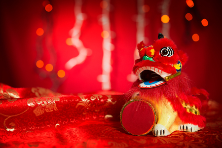 New years party: Chinese new year decorations, miniature dancing lion on red glitter background.