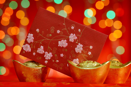 ang: Chinese new year decorations, red packet and gold ingots on red glitter background.