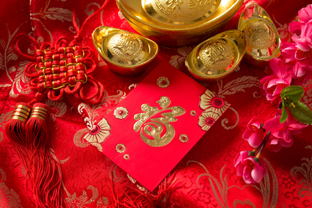 Chinese new year festival decorations, red packet and gold ingots. Chinese character means good fortune, not logo and copyright. Stock Photo
