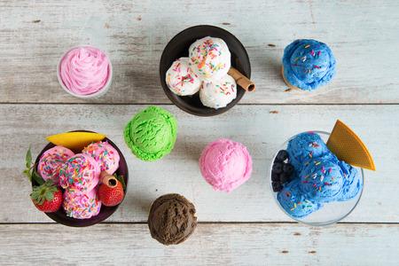comiendo helado: Vista superior de fresas, arándanos y helado de vainilla en un tazón en el fondo blanco de madera rústica.