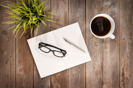 Top view workplace with planner, pen, eyeglasses, plant pot and hot coffee cup. Wooden table background with copy space in vintage toned.