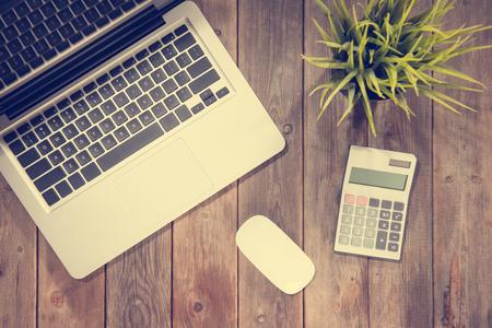 calculadora: Vista superior de la mesa de trabajo con ordenador portátil, calculadora y maceta. fondo de la tabla de madera con espacio de copia en la vendimia entonada. Foto de archivo