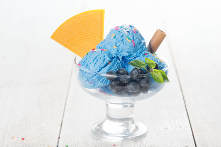 Blue ice cream in cup with blueberry fruits and waffle on white rustic wooden background.