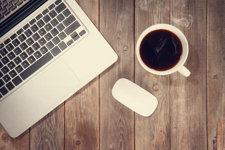 artistas: Mesa de trabajo de madera con ordenador portátil, taza de café caliente, en tonos tonos de vintage de luz dramática.