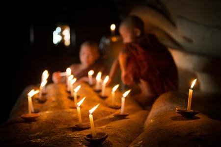 luz de velas: Poco monjes novicios mano que sostiene una vela en el interior del templo, Bagan, Myanmar.