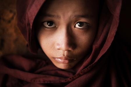 volto uomo: Chiuda sul fronte di giovane monaco novizio ricoperto di manto, di scarsa luminosit� con la regolazione del rumore, Bagan, Myanmar.