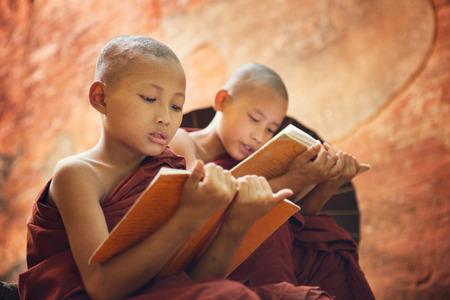 burmese: Young Buddhist novice monk reading and study outside monastery, Myanmar. Stock Photo